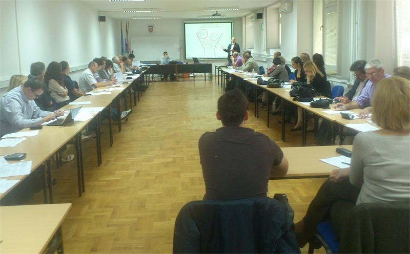 Slika prikazuje sudionike radionice održane u prostorijama Ministarstva uprave, oko 40-ak sudionika.
